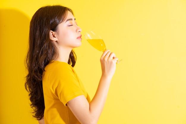 ワインを飲み、黄色でポーズをとる若いアジアの女性