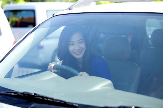 若いアジアの女性が運転