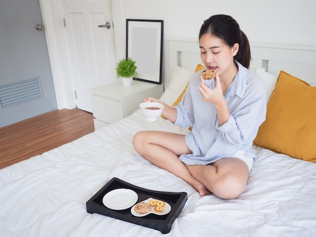 Young asian woman eat coffee cookie on bed