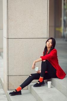 Молодая азиатская женщина ест фаст-фуд на открытом воздухе