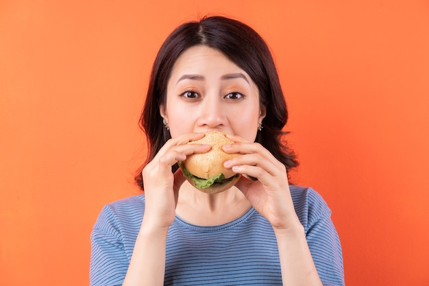 Young asian woman eating hamburger on orange