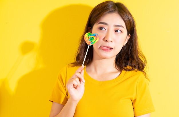 노란색에 막대 사탕을 먹는 젊은 아시아 여성
