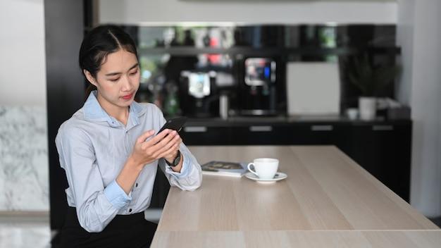 Молодой азиатский работник женщины используя мобильный телефон во время перерыва на кофе в офисе.