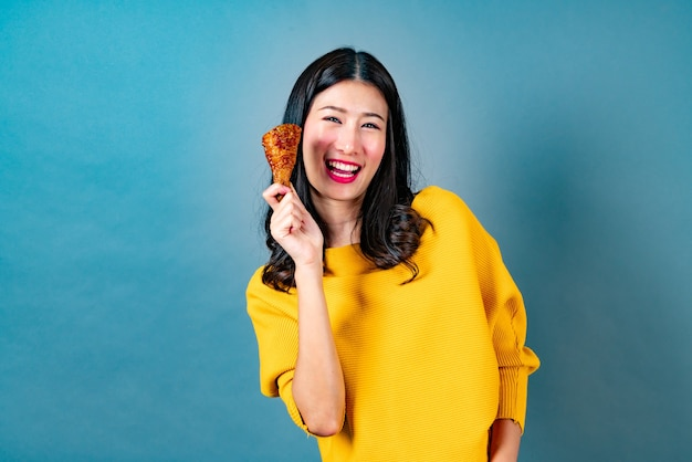 젊은 아시아 여성 프라이드 치킨 드럼 스틱을 먹고 즐길 수
