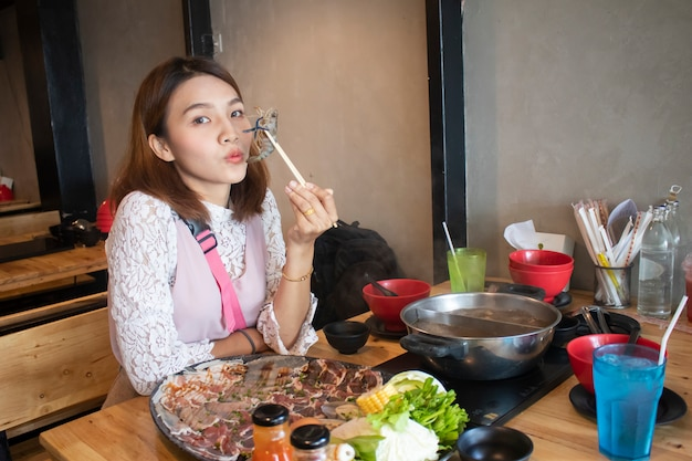 Young asian woman enjoy eating shabu-shabu japanese hot pot