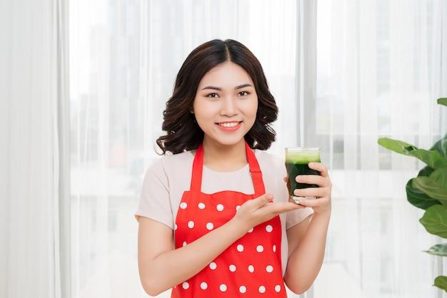 若いアジアの女性は減量とデトックスのために健康的なベジタリアンスムージーを楽しんでいます Premium写真