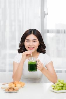 젊은 아시아 여성은 체중 감량과 해독을 위해 건강한 채식 스무디를 즐깁니다.