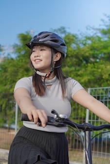 여름 아침에 멈췄을 때 사이클링을 즐기는 젊은 아시아 여성