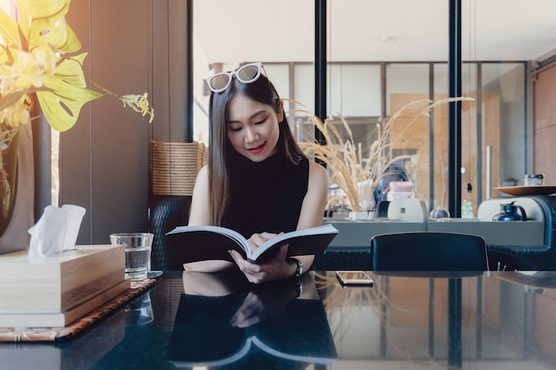 Young asian woman enjoying reading book while sitting at home
