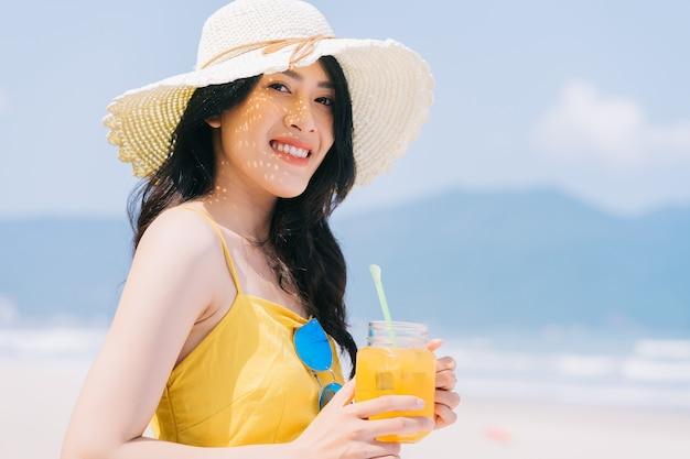 ビーチで夏休みを楽しんでいる若いアジアの女性