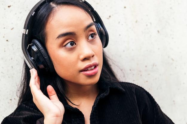 젊은 아시아 여성은 야외에서 콘크리트 벽에 기대어 헤드폰을 끼고 음악을 듣는 것을 즐깁니다.