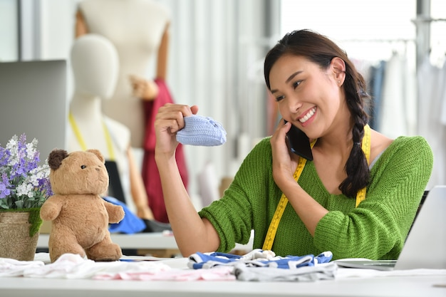 Young asian woman entrepreneur / fashion designer for baby clothes working in studio