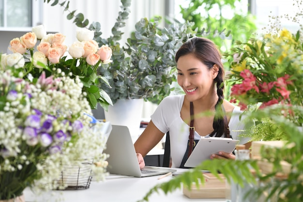 Young asian woman entrepreneur/shop owner/ florist of a small flower shop business