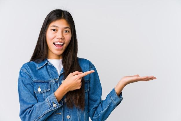 若いアジアの女性は手のひらにコピースペースを持って興奮しました。