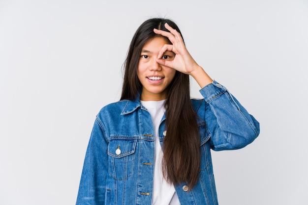 Молодая азиатская женщина возбужденная держащ одобренный жест на глазе.