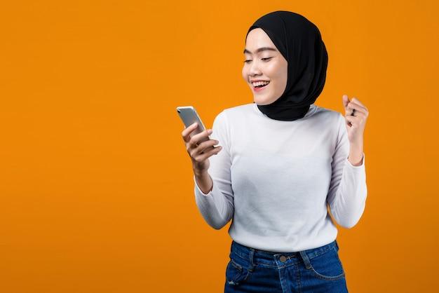 휴대 전화를 사용 하여 흥분된 젊은 아시아 여성