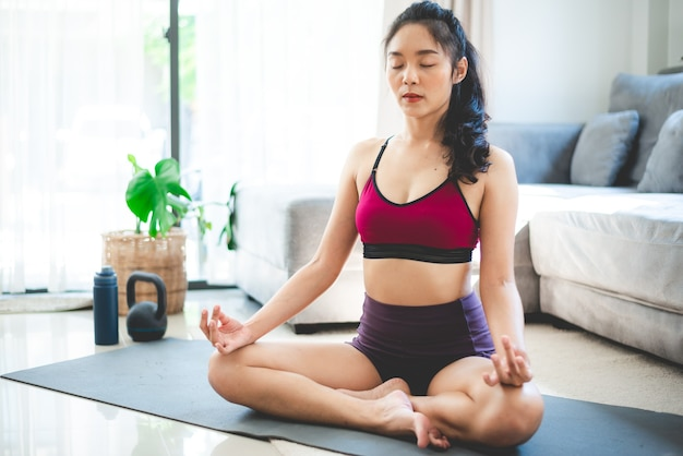 Молодая азиатская женщина, занимающаяся йогой в домашнем тренажерном зале, здоровый женский образ жизни с фитнесом и спортивными тренировками дома, девушка делает активные физические упражнения в закрытом помещении дома, релаксация и хорошее самочувствие