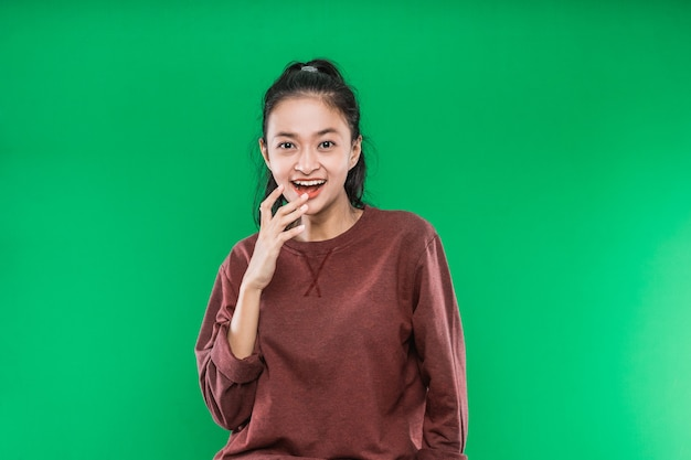 Молодая азиатская женщина выражает счастливый широко открытый рот и поднимает руки на подбородке, изолированном на зеленом фоне