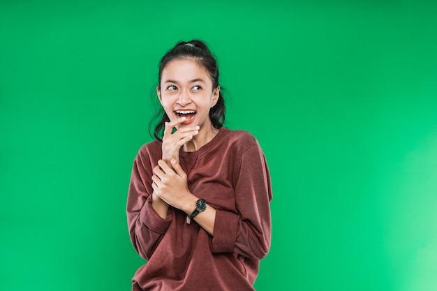 Молодая азиатская женщина выражает счастливый широко открытый рот, глядя рядом и поднимая руки на подбородке на зеленом фоне
