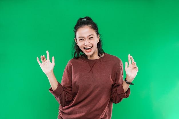 Молодая азиатская женщина выражает счастливый широко открытый рот, глядя в камеру, заставляя ладони подниматься, открываясь на зеленом фоне