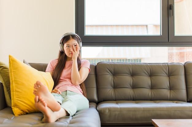Молодая азиатская женщина чувствует скуку, разочарование и сонливость после утомительной, скучной и утомительной работы, держа лицо рукой