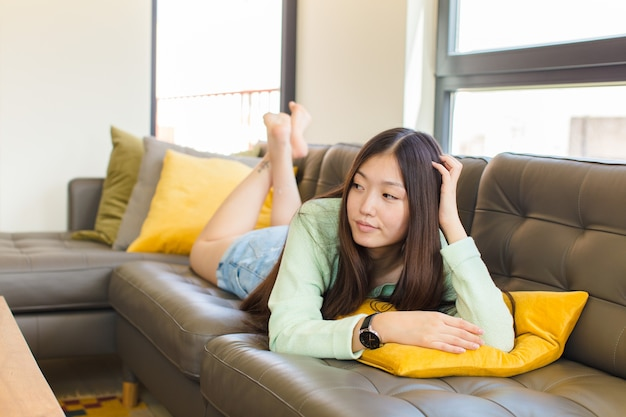 Young asian woman feeling clueless and confused, thinking a solution, with hand on hip and other on head, rear view