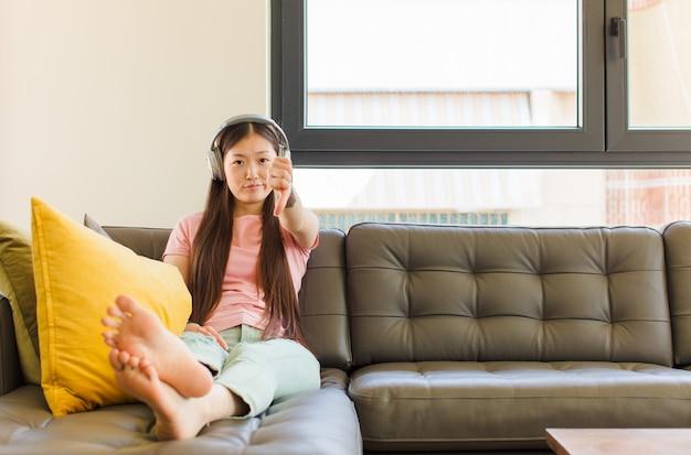 若いアジアの女性は、真剣な表情で親指を下に見せて、十字架、怒り、イライラ、失望または不満を感じています