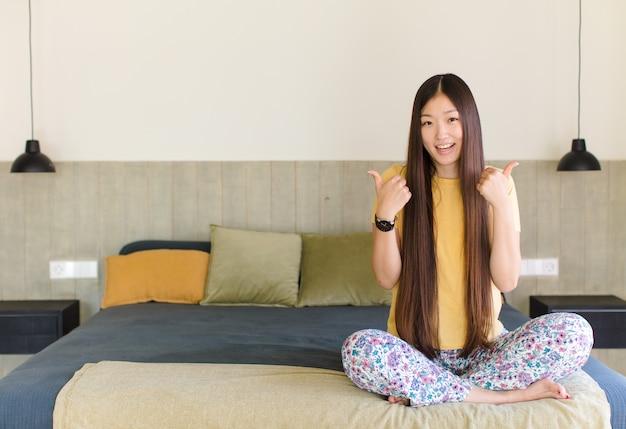 十字架、怒り、イライラ、失望または不満を感じ、真剣な表情で親指を下に見せている若いアジアの女性