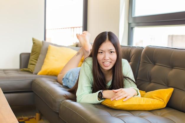 嫌悪感とイライラを感じ、舌を突き出し、厄介で厄介なものを嫌う若いアジアの女性