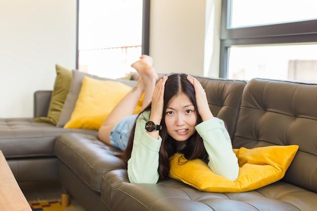 Молодая азиатская женщина чувствует себя разочарованной и раздраженной, больной и уставшей от неудач, сытая по горло скучными, скучными задачами