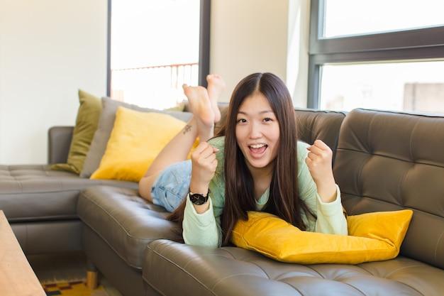 幸せ、前向き、成功を感じ、勝利、成果、または幸運を祝う若いアジアの女性