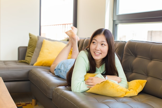 Young asian woman feeling happy, proud and hopeful, wondering or thinking, looking up to copy space with crossed arms