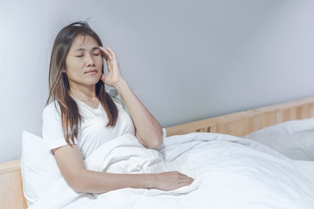 Young asian woman feeling headache and discomfort on white bed in her bedroom.