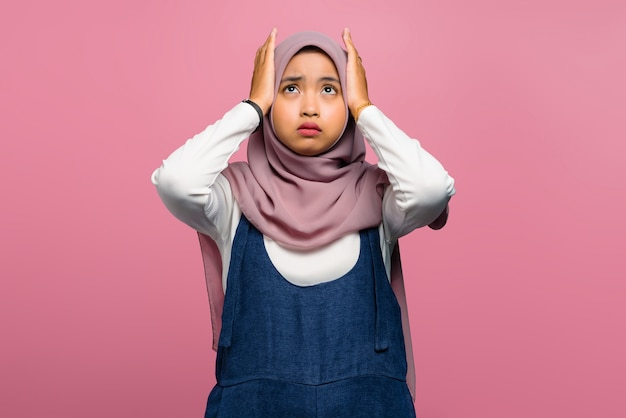 Young asian woman feeling headache on pink background