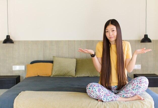 Молодая азиатская женщина чувствует себя озадаченной и сбитой с толку, неуверенной в правильном ответе или решении, пытаясь сделать выбор