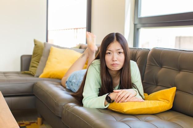 Молодая азиатская женщина чувствует грусть и стресс, расстроена из-за неприятного сюрприза, с негативным, тревожным взглядом