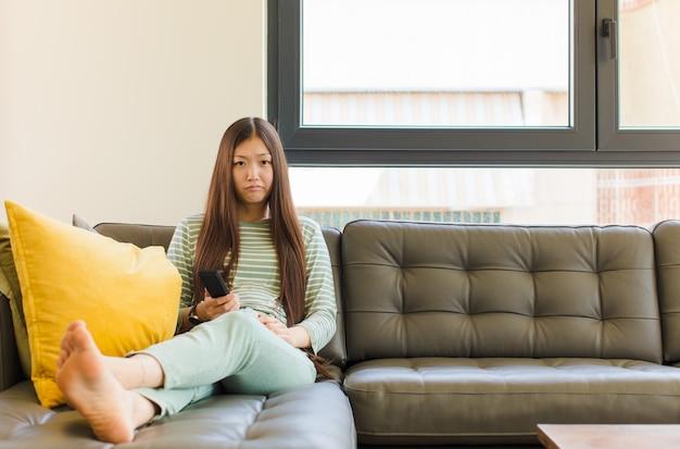 不幸な表情で悲しみと泣き言を感じ、否定的で欲求不満の態度で泣いている若いアジアの女性