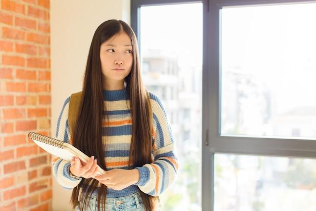 젊은 아시아 여성이 슬프거나 화가 나거나 화가 나고 부정적인 태도로 측면을 찾고, 불일치에 찌푸린
