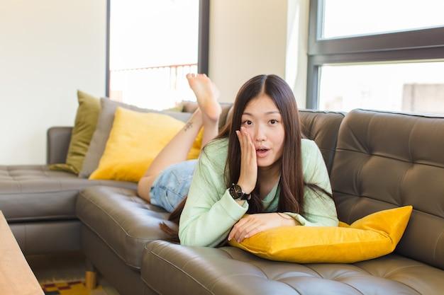 Молодая азиатская женщина чувствует себя потрясенной и изумленной, держась за руки в недоумении с широко открытым ртом