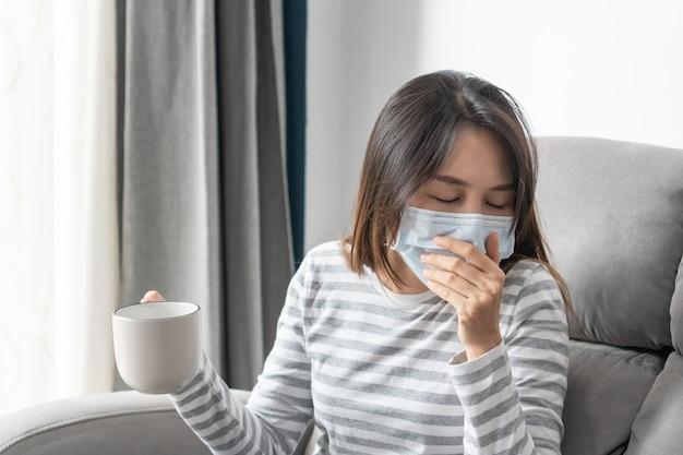 집에서 감기와 열에 시달리는 젊은 아시아 여성, 안면 마스크를 쓴 아픈 소녀는 거실 소파에 앉아 두통과 기침을 합니다. 건강 문제 개념입니다.