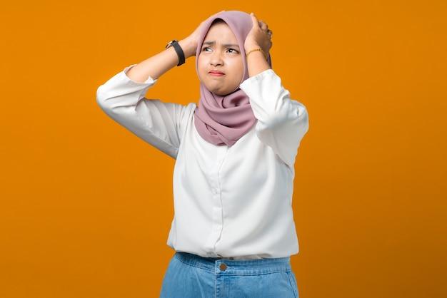 黄色にストレスを感じる若いアジアの女性