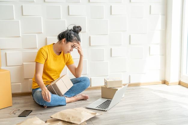 Молодая азиатская женщина чувствует стресс или депрессию перед своим ноутбуком - концепция онлайн-продаж