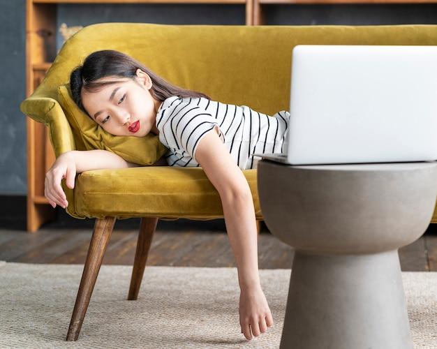 Молодая азиатская женщина заснула на диване перед ноутбуком
