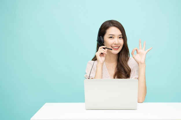 Young asian woman friendly operator agent with headsets and showing ok sign working on light green background