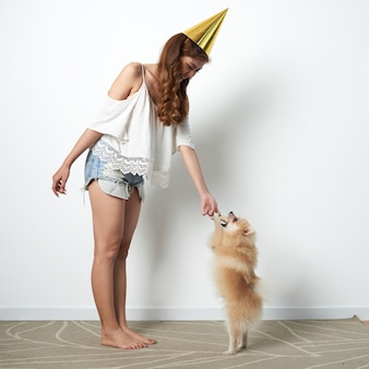Young asian woman in fun party hat playing at home with small pet dog