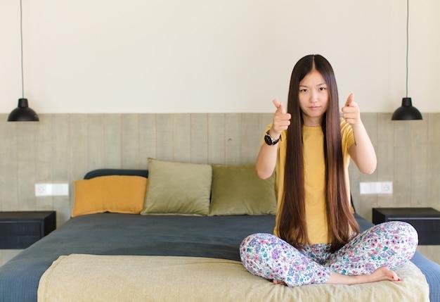 若いアジア人女性が猛烈に叫び、ストレスを感じ、空中に手を上げてイライラし、なぜ私が