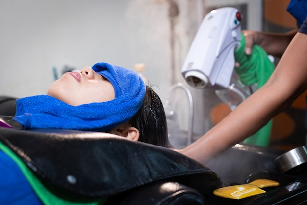Молодая азиатская женщина, получающая мытье волос и спа-процедуру парикмахером в парикмахерской. парикмахер делает лечение и спа-прически молодой женщины. салон красоты, уход за волосами и концепция образа жизни людей.