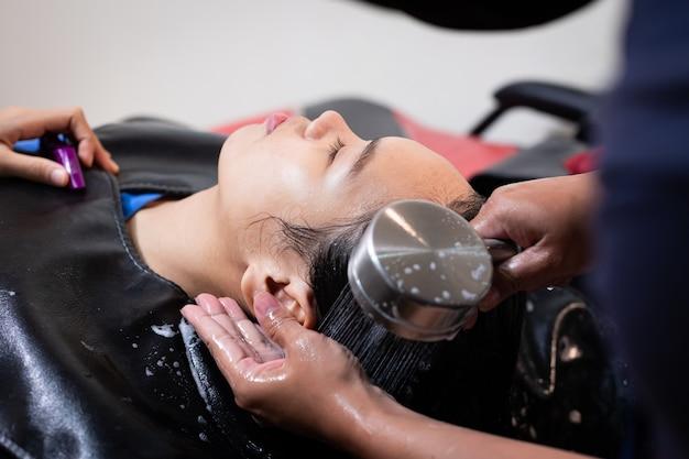 Молодая азиатская женщина получая мытье волос парикмахером в парикмахерской. парикмахер, мытье волос молодой женщины. салон красоты, уход за волосами и концепция образа жизни людей.