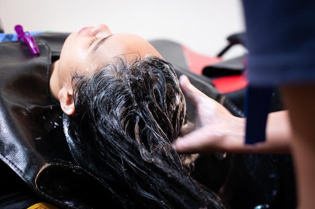 Молодая азиатская женщина получая мытье волос парикмахером в парикмахерской. парикмахер моет волосы молодой женщины шампунем и массирует ее голову.