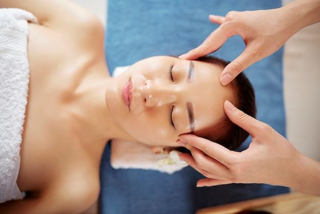 Молодая азиатская женщина получает массаж лица